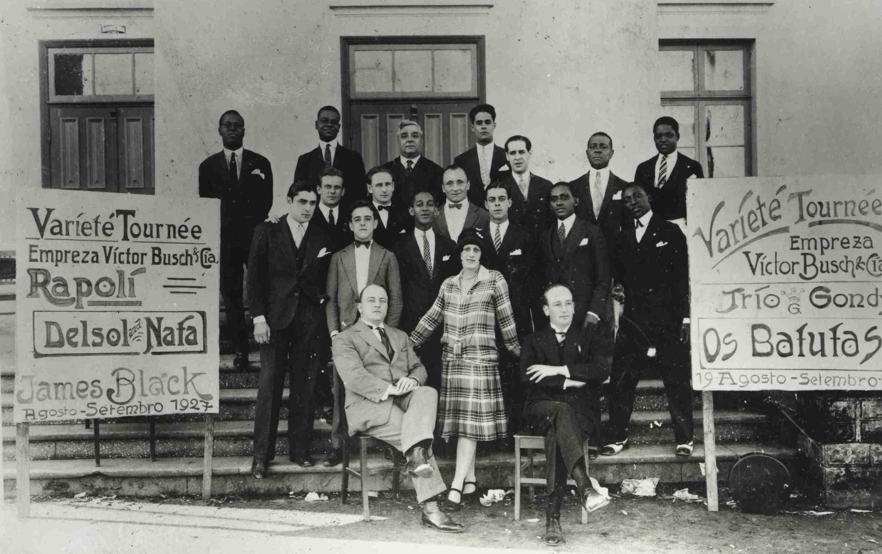 """Donga e Pixinguinha (fila de trás, o primeiro e o segundo da esquerda para a direita), Bonfiglio de Oliveira (fila do meio, o segundo da direita para a esquerda) e pessoas não identificadas. O cartaz à direita anuncia apresentação do grupo """"Os Batutas"""". Joinville (SC), 07/09/1927 (MIS_SCabral_103900 / Acervo Sérgio Cabral / MIS-RJ)"""