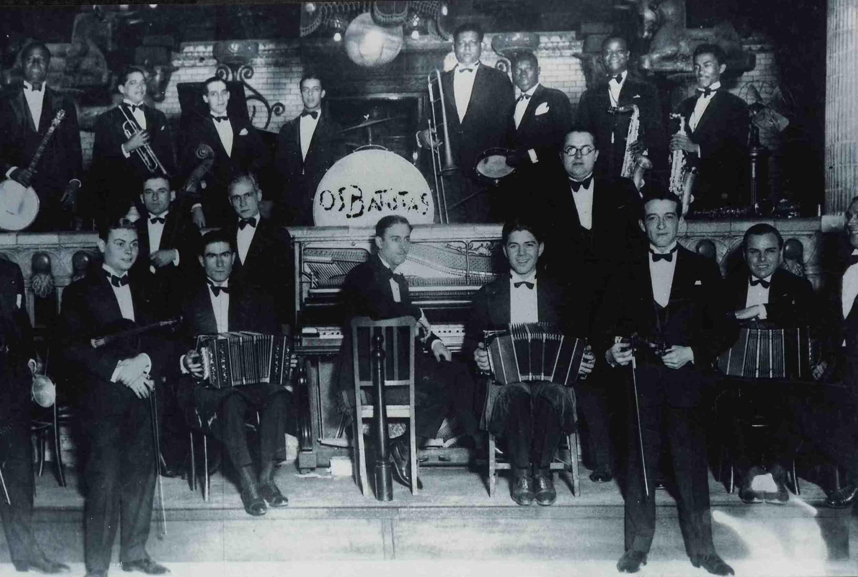 Restaurante Assyrius, no Theatro Municipal do Rio de Janeiro. Os Batutas na fila de trás, Pixinguinha é o segundo à direita, com o saxofone. Na fila da frente, provavelmente, a Orquestra Andreoni. (MIS_SCabral_103270 / Acervo Sérgio Cabral / MIS-RJ)