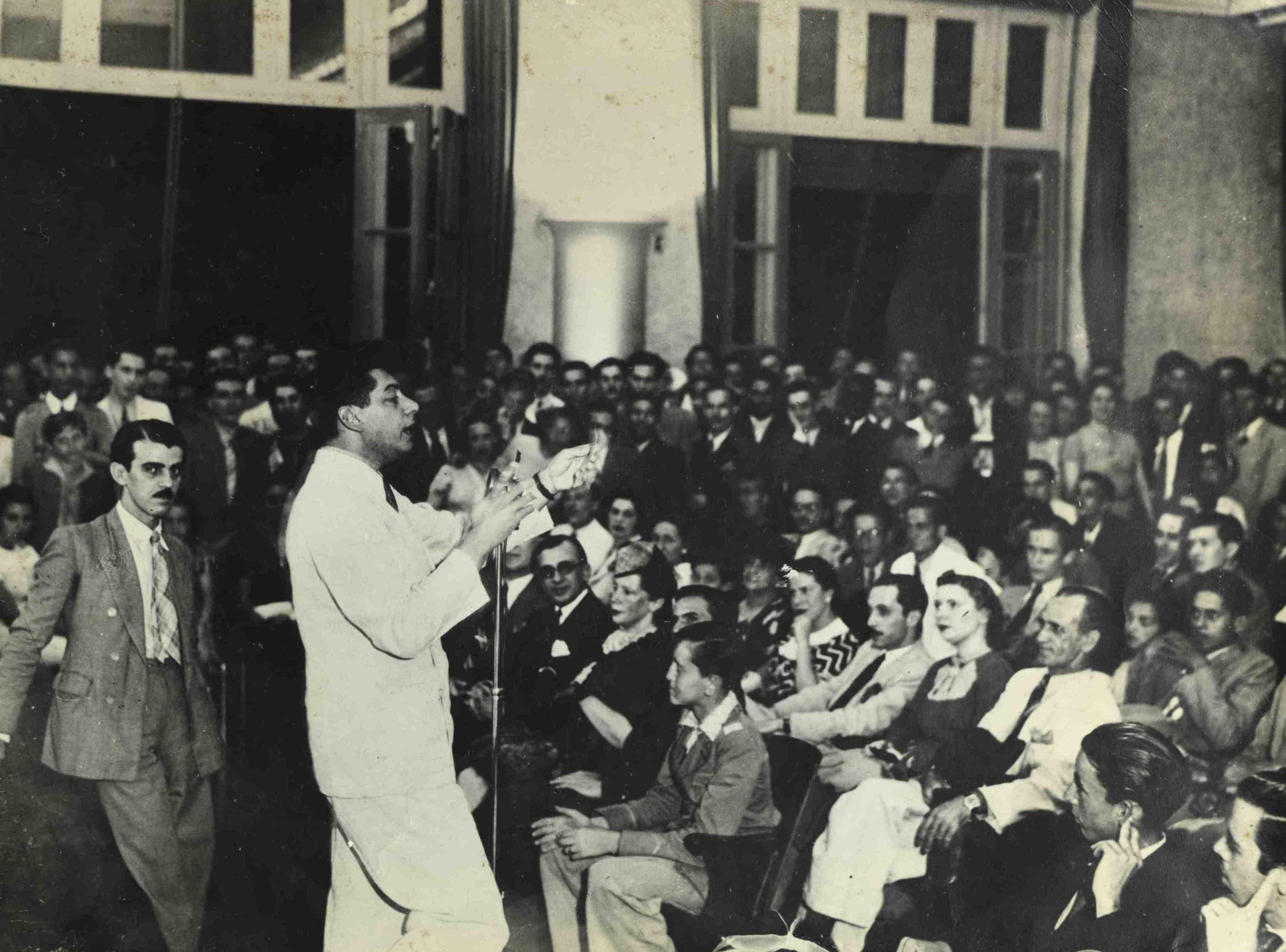 Almirante ao microfone no auditório da Rádio Nacional. Praça Mauá, Rio de Janeiro (MIS_Alm_041252 / Acervo Almirante / MIS-RJ)