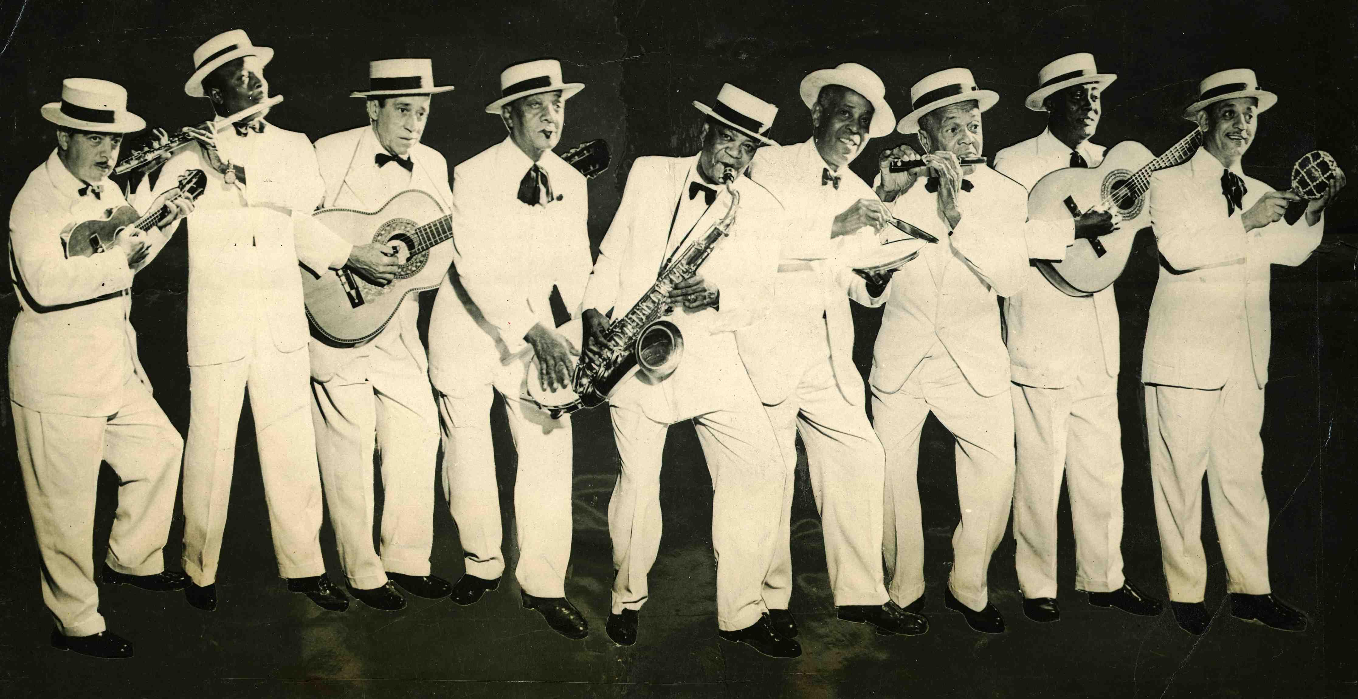 """Grupo da Velha Guarda. Foto de divulgação do show """"O samba nasce no coração"""", produzido por Zilco Ribeiro na boate Casablanca. Da esquerda para a direita: Waldemar de Melo (cavaquinho), Bide da Flauta, Rubem Bergman (violão), João da Bahiana (pandeiro), Pixinguinha (saxofone), Donga (prato e faca), Alfredinho Flautim, Mirinho (violão) e J. Cascata (afoxé). Boate Casablanca, Urca, Rio de Janeiro, 1955 (IMS_JRT_pixinguinha050 / Acervo Tinhorão / IMS)"""
