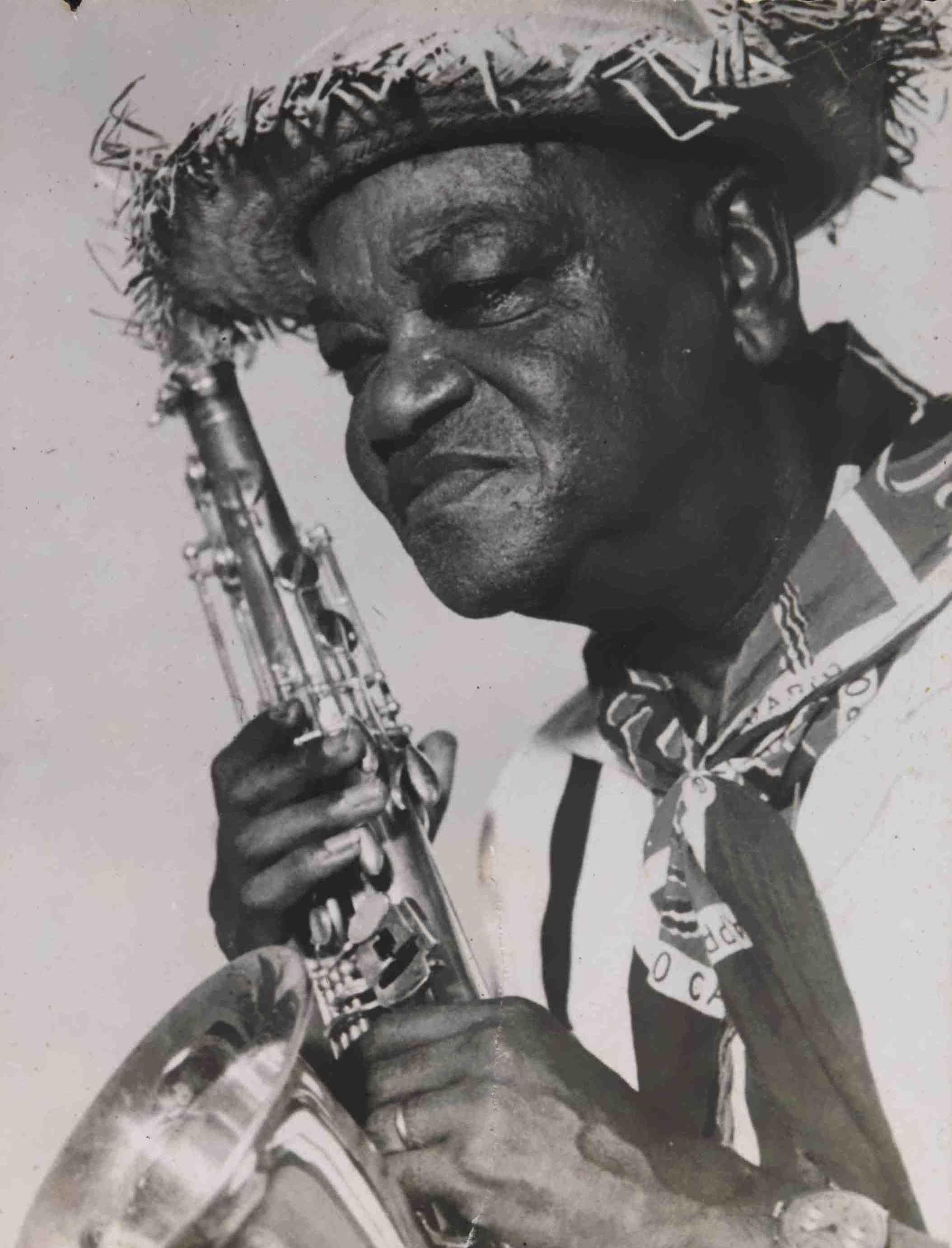 Pixinguinha, com seu saxofone, vestido de caipira (com chapéu de palha e lenço no pescoço) para sessão de fotos feita para a capa do LP Pixinguinha e sua banda (RCA Victor, 1957), com repertório formado apenas por músicas juninas (MIS_JBandolim_238 / Acervo Jacob do Bandolim / MIS-RJ)