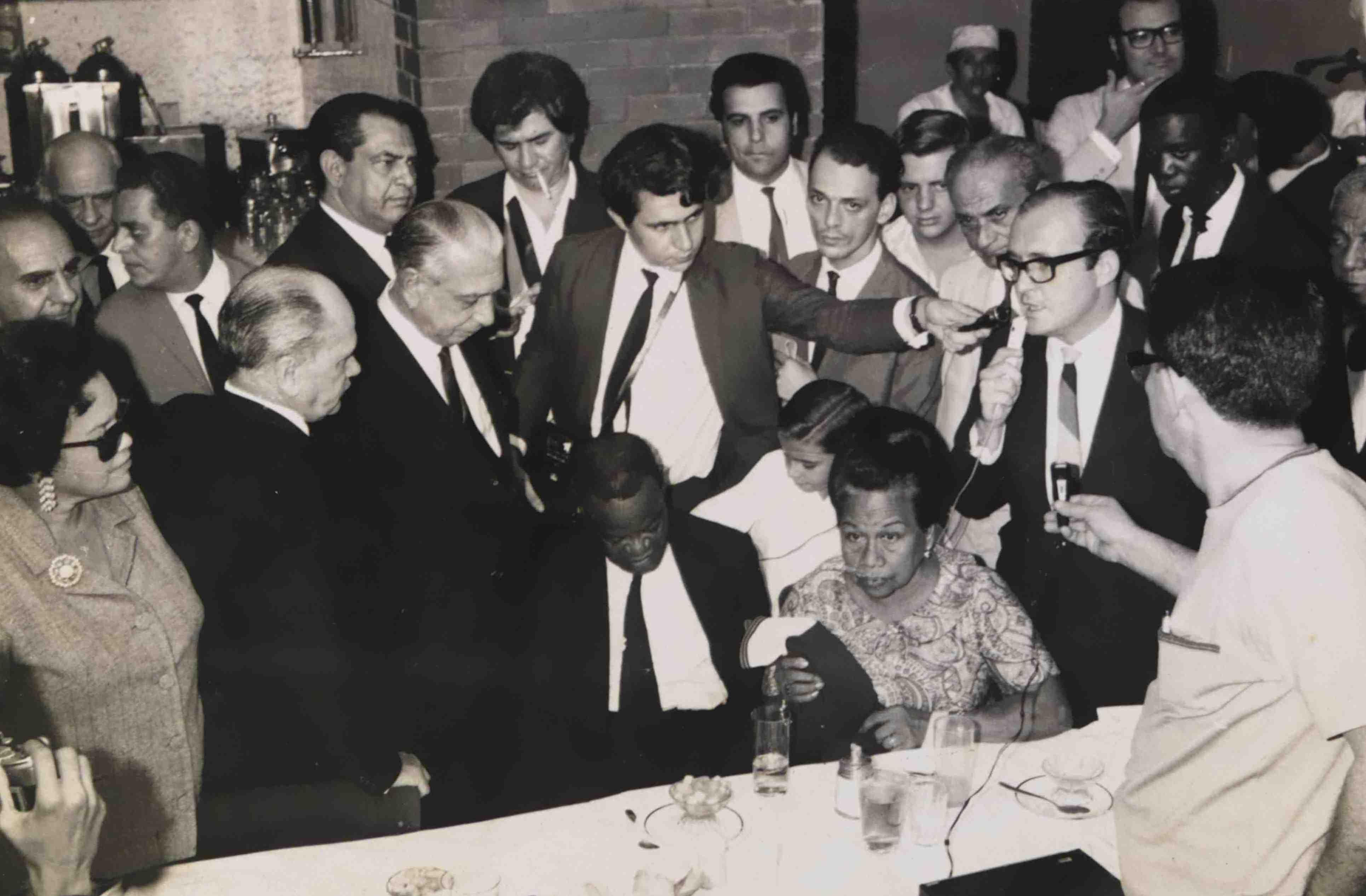 Pixinguinha e Betty (sentados) durante comemoração pelo 70º aniversário de Pixinguinha (que na verdade fazia 71 anos). Em pé, à direita de Pixinguinha, está Negrão de Lima, governador da Guanabara, Jacob do Bandolim em frente a Betty e Ricardo Cravo Albin à sua esquerda. Churrascaria Tijucana, Rio de Janeiro, abril de 1968 (MIS_JBandolim_474 / Acervo Jacob do Bandolim / MIS-RJ)