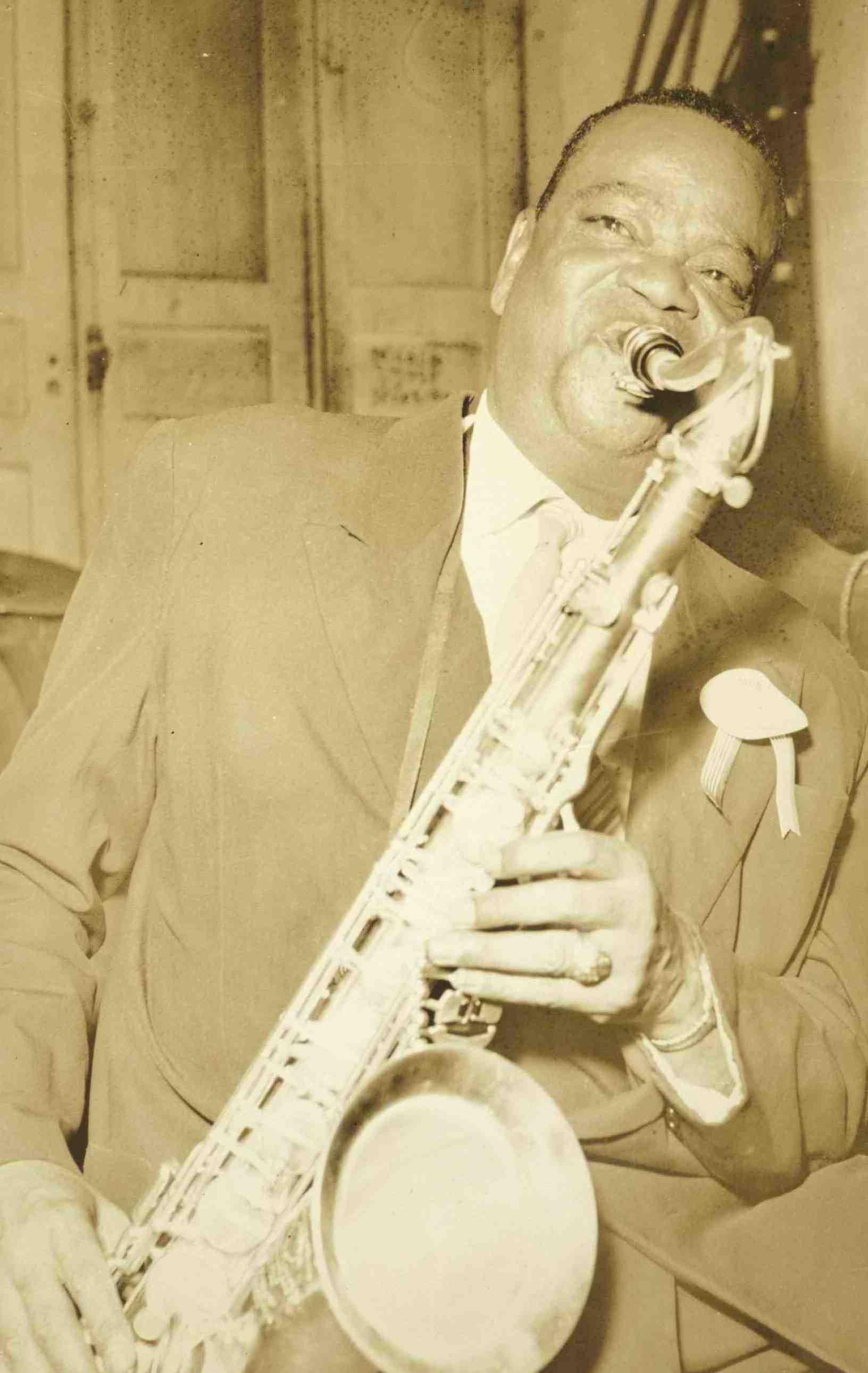 Pixinguinha tocando saxofone. Na lapela, a condecoração recebida por ocasião dos Festivais da Velha Guarda. São Paulo, 1954 ou 1955 (MIS_MIS_116745 / Acervo MIS-RJ)